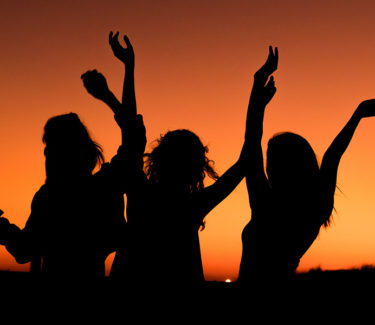 Silhouette of three girls against a sunset