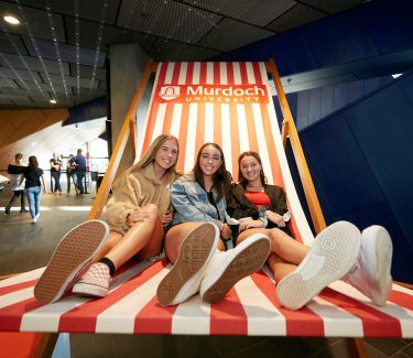 Three girls sitting on a giant deckchair