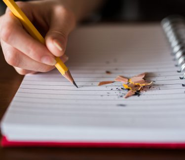 Person writing in a notebook with lead pencil